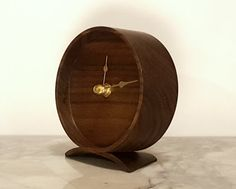 There is something so appealing about the design of vintage wind up alarm clocks. Using elements of that classic design, but with an all wood construction allows this clock to be used outside the bedroom, as a simple aesthetic timepiece. The clock shown here is made of walnut, however, I also make them out of cherry, maple, and white oak. You may choose between black hands with a silver coloured handle on the back, or brass hands with a solid brass handle. It measures 3 7/8 inches in di...