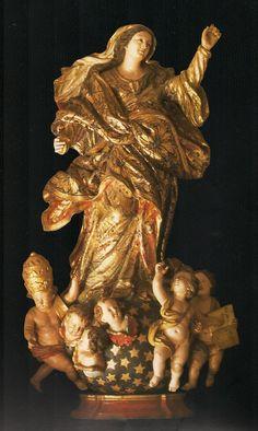 """Nossa senhora da Fé - Imagem vinda de Portugal, no século XVII, em madeira policromada e dourada. A virgem está de pé sobre peanha que figura o orbe celeste ao qual estão sobrepostos querubins e 3 anjos. Um deles usa venda nos olhos, simbolizando a total entrega que exige a fé. (A fé é cega); outro apresenta um livro aberto onde se lê """"Tota pulchra es MARIA"""" e o terceiro deles usa a tiara pontifícia. Esta imagem encontra-se na Sacristia da Catedral Basílica da cidade do Salvador. Bahia…"""