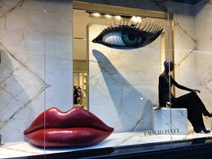 Window Display at the Emilio Pucci store, Madison Avenue at 71st Street in New York, Against a marble backdrop, a single mannequin in a black dress is dominated by a loveseat-size set of red lips, & a single eye dangling from the ceiling.  It's a bit Surrealist for Pucci, but a whimsical way for a luxury retailer to enter the strip when everyone else is putting up their holiday windows.
