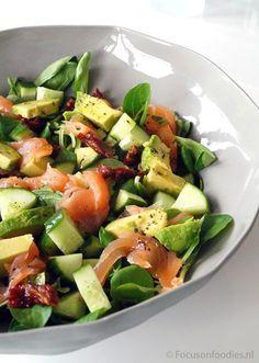 frisse salade met gerookte zalm, avocado en komkommer, Nodig: 200gr gerookte zalm,150 gr veldsla,1/2 komkommer,1 avocado,10 zongedroogde tomaten,maak een dressing van 2 a 3 el olijfolie,sap van 1/2 citroen,1 tl dille,zout en peper.