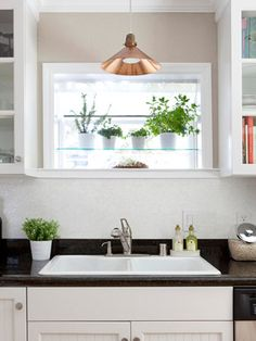 Custom Look Vintage Accents: With a few smart additions, the homeowners updated the sink area at minimal cost. The builder-grade sink and faucet were replaced with more upscale models. A new windowsill and a mosaic tile backsplash add style. The space was finished with a copper pendant light, a lucky flea market find.