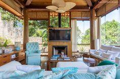 Poltrona Berger na cor azul e sofás brancos com almofadas estampadas.