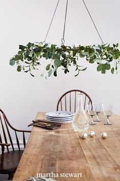Rather than tucking mistletoe in a doorway, make family meals warm and fuzzy with an overhead centerpiece. Wrap a wreath frame with fresh eucalyptus and faux mistletoe (toxins in the real berries can harm kids and pets), and attach ornaments with floral wire. #christmas #holidayideas #christmasideas #wintertodo #marthastewart