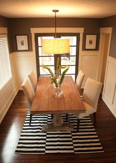 Stunning dining room with chocolate brown walls paired with board and batten. Linen drum pendant over World Market Provence Dining Table with linen Parsons dining chairs over black and white striped rug layered over wood floors.