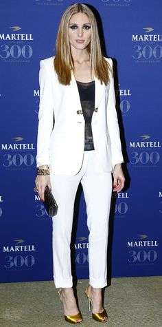 Olivia Palermo suited up for Martell Cognac's 300th anniversary event, teaming her crisp white separates with a sheer black top, a chunky gold bracelet, a gunmetal Hayward clutch, and yellow satin sling-backs.