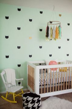 Applying fun decals to the wall is an inexpensive and commitment-free way to add some visual interest to the room. In this bright and modern nursery, adorable cat decals line the wall where the crib is placed. Plus, using colors and decals like these make this space a fairly gender-neutral nursery. Click through for more on this and other unique nursery decorating ideas.