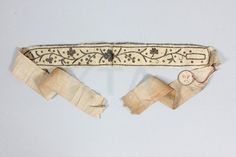 Embroidered silk garter, French, late 18th century, ivory silk couched with silver thread and sequins.