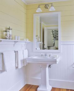 The yellow-and-white palette of the bedroom carries into the adjoining bath. Built-in ledges hold toiletries. - Traditional Home ®