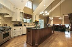 Soaring vaulted ceiling over this wide open kitchen includes upper windows for maximum natural light. Lengthy dark wood island with black countertop contrasts with white painted cabinetry and beige countertops with matching tile backsplash.