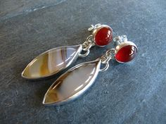 These earrings are made with lozenge shaped Montana agates set in fine and sterling silver settings. The stones are translucent with typical streaks of brown and amber. The Montana agates dangle from 8mm round deep orange carnelians. The post and ear nut are sterling silver. 1 5/8 (40mm) from top to bottom. Lovely