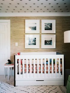 Modern eclectic nursery (alternate view) the black and white photos remain adult but the papered ceiling add childlike whimsy. The black and orange tying in to the opposite wall.