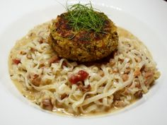 crab cake atop a bowl of tagliatelle pasta, tossed with an andouille sauce