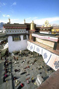 Pilgrims prostrating before entering the Johkang Temple, Lhasa, Tibet