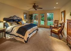 This buttercream master bedroom features a traditional bed and headboard with black and white bed linens and floral pillows. Two wooden armchairs with striped cushions create a relaxing sitting area, while a glass door provides access to the outdoor patio area.