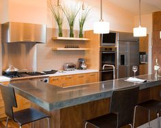 Interior Design, Contemporary Kitchen With Long Woden Kitchen Table With Stunning Black Concrete Countertops Also Dark Brown Kitchen Chairs Also Comely Pendant Lights And Cool Modern Exhaust Hood And Cooker Also Kitchen Shelves: The Black Concrete Countertops for Your Kitchen