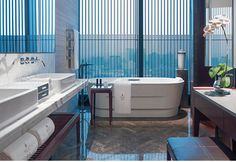 NUO STUDIO Separated by sliding screen doors and bathed in natural light, the marble bathroom invites you to soak in its oval bathtub with views across the city, as you ponder lines of poetry by Ming scholar Wen Zhengming, carved delicately into the wall.