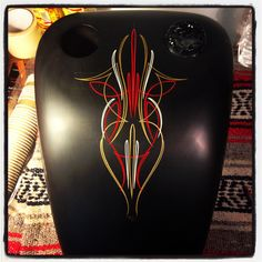 Pinstriping in gold, red and ivory on widened sportster tank.