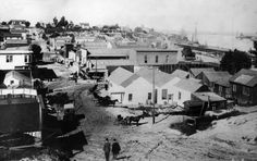 (late 1800s)* - View of an unpaved road with horses and carriage in San Pedro. The harbor can be seen in the distance.