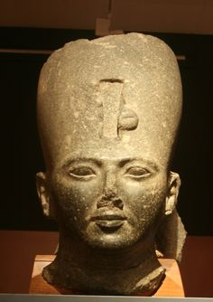 Granodiorite head of Rameses II from Bubastis, Lower Egypt dated as New Kingdom ( 1279 - 1213BCE ) and housed at the Nicholson Museum, University of Sydney, Australia. The black granite head of Ramesses II originally came from a larger statue & is of monumental scale. The head is supported by a back pillar which bears the remains of three hieroglyphic signs. There is evidence that suggests re-use ( remodeling ) the bust could have been of a previous ruler Amenhetep III.