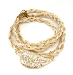 A toffee satin cord and a gold chain are braided together in this wrap bracelet with a stunning Swarovski crystal encrusted gold leaf.  The bracelet is 21 inches long and will wrap around your wrist three times.