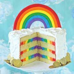 This gorgeous Rainbow Cake features moist yellow cake, striped rainbow frosting inside, and a light and fluffy cloud-like meringue on the outside!
