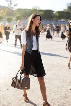 Shop this look for $136:  http://lookastic.com/women/looks/crew-neck-t-shirt-and-vest-and-midi-skirt-and-wedge-sandals-and-duffle-bag/2452  — White Crew-neck T-shirt  — Navy Denim Vest  — Black Pleated Chiffon Midi Skirt  — Brown Suede Wedge Sandals  — Brown Leather Duffle Bag