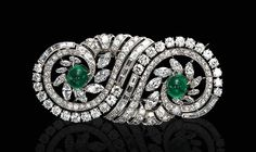AN ART DECO DIAMOND AND EMERALD DOUBLE CLIP BROOCH  Each designed as a marquise, baguette and old European-cut diamond scroll, centering upon a cabochon emerald, mounted in platinum, circa 1930