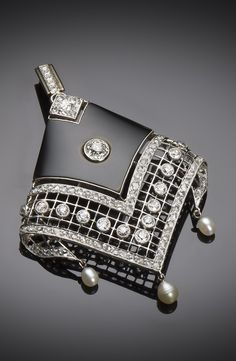 An Art Deco platinum, gold, diamond, onyx and pearl pendant, circa 1930.
