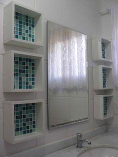 Nichos de madeira com pastilhas de vidro para organizar o banheiro de um jeito delicado.