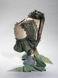 Capote, 1860; Natural straw, ribbons of green silk taffeta, black machine made Chantilly Lace, green paper. Paris, Galliera - Fashion Museum of the City of Paris