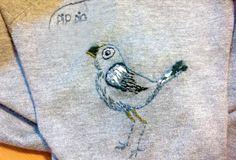 Næbbet er fyldt ud med fladsting. Øverst på vingen er der franske knuder. Fuglens kontur er broderet med stikkesting. Du behøver bare at kunne tre sting, så kan du forvandle en ordinær cardigan til en personlig cardigan  med en glad pipfugl.
