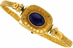 Etruscan Revival Lapis Lazuli, Gold Bracelet The bracelet features an oval-shaped lapis lazuli measuring 12.50 x 9.00 x 3.00 mm and weighing approximately 2.50 carats, set in textured 22k gold. Gross weight 20.90 grams.