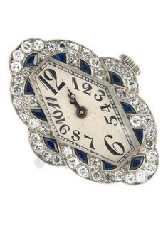 An Art Deco platinum sapphire and diamond ring watch. The hexagonal-shape silvered dial with graduated Arabic numerals and minutes track, to the single-cut diamond and fancy-shape sapphire geometric surround, with foliate engraved sides and plain band. Estimated total diamond weight 1ct. Length of ring head 2.8cms. Weight 11.7gms.
