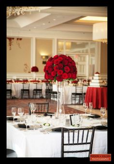 Love the center piece and the use of black with the napkins, I would add a bit more red to the table though