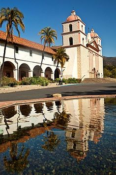 The Old Mission in Santa Barbara California is reflected in a fountain's…