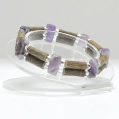Healing Hazelwood and amethyst gemstone double bracelet. On elastic. Grown in Quebec, Canada. Hazelwood gives natural pain relief when worn. It is useful in ailments such as acid reflux, eczema,  heartburn, constipation & acne. In order to receive a  therapeutic benefit the necklace must be worn as much as possible. No chemicals of any kind (pesticides, fertilizers, etc.) are used to grow the  hazelwood trees these necklaces are made from.