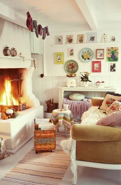 White walls, pictures, plants, firewood in metal bucket, hand-knit socks handing to dry, old-fashioned alarm clocks, fireplace, crochet blankets, antique sofa, vintage pillows, fur blanket, crate on wheels, striped linen rug - everything. Fresh, bright, and airy, but warm, snug, and cozy at the same time.