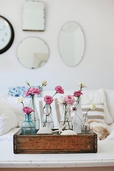 Mirrors, mixed glass vases in seafoam colors with various silk flowers