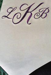 Royal purple script 3-letter monogram on white satin.