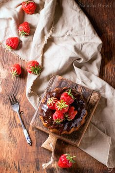 Chocolate Cake with Strawberries - Homemade chocolate cake with strawberries and dark chocolate ganache, served on small wooden cutting board over wooden table with gray textile. Top view