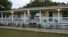 fully covered front porch on double wide -- like the rustic tin as skirting.