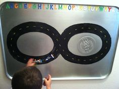 Paint a race track with acrylic paint onto an oil drip pan, cover with clear coat spray paint. Attach magnet strips to toy cars and you have a fun race track!