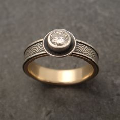 A sterling silver spiral patterned engagement ring with 14k yellow gold lining and a 4.5mm tube-set diamond.