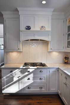 Gas cooktop with under cabinet lighting, built-in hood.