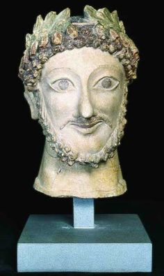 Male Head Cypriot 5th Century BC The male head from Athienou, near the important Phoenician town of Golgoi, probably depicts a priest of the Aphrodite cult, as witness his rich and brightly colored crown of laurel leaves and berries intertwined with pomegranate buds. The sharp lines of the face, the large almond-shaped eyes and the smiling mouth place the head in the classical-Cypriot style of the 5th century B.C Source: Museo di Scultura Antica Giovanni Barracco
