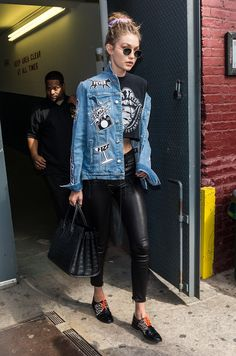 Gigi Hadid wears a denim jacket, black leather pants, and a black T-shirt