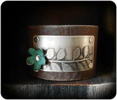 Una pulsera brazalete de cuero con un diseño de hoja grabado acentuado con una flor de latón offset. Tiene un cierre de botón elástico. Mide 1 1/2