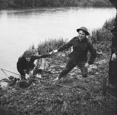 The Home Guard: After swimming a river in full kit during an exercise in Yorkshire, a helping hand is extended to a member of Number 2 Platoon 'B' Company of the 4th Battalion, East Riding Home Guard.