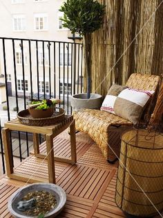 Cozy balcony corner with a wooden side table and basket chair on a wooden floor – living4media