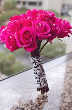 Fuchsia Hot Pink Roses with Damask ribbon wrapped around the roses and diamond pins to accent the flowers. Beautiful Bouquet.